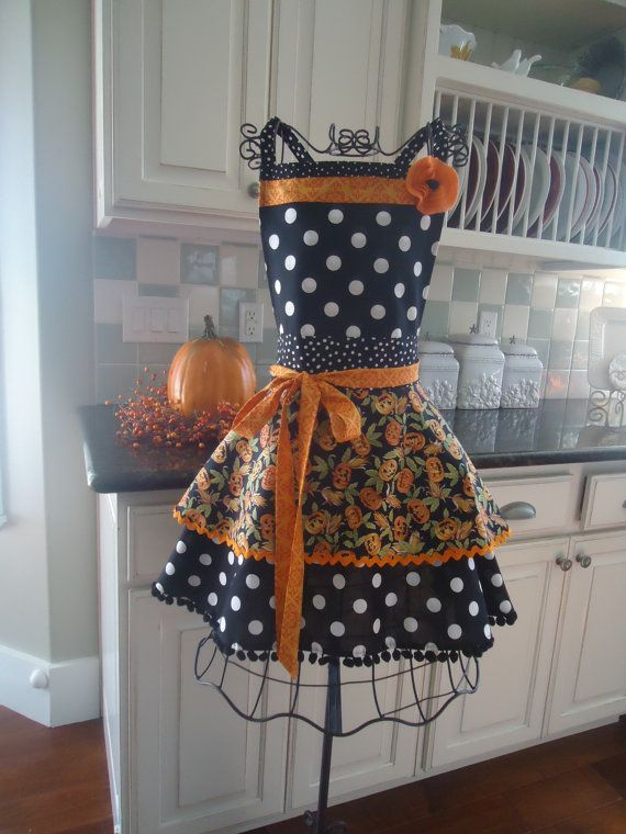 Our Annabelle Full Apron in Harvest Fall Style! Black, tangerine/orange with pumpkins, pom poms and polka dots! This one does not come with pockets..... If you want a pocket, please request one on the order!    You will love to greet your guests in style! Ties around the neck and waist to fit a variety of sizes from 4 to 10. Please email for availability for smaller or larger sizes. Flower can be easily removed. Beautifully handcrafted by a mom and her daughters in a smoke-free/pet-free…