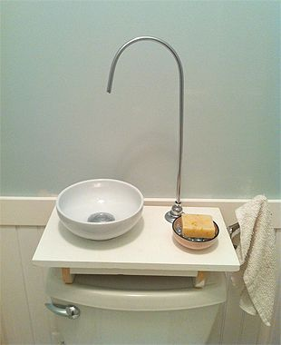 "this all-in-one solution puts a hand-washing sink over the toilet tank. It also saves money by channeling used ""greywater"" into the tank for flushing the toilet! A lever on the side of the little counter controls water to the faucet."