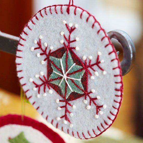Beginning sewers will have fun creating this simple circle-shape ornament; adorn with snowflakelike designs or other seasonal images, such as trees and candy canes. Start by cutting two circles of felt; attach together using a blanket stitch. Use contrasting felt colors to add designs; here, a star shape is overlaid onto a small hexagon, and straight stitches and French knots provide decorative elements. Create a hanging loop with a longer piece of knotted thread.