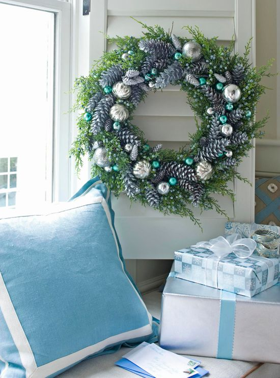 Blue and silver are a classic holiday  color combination. Experimenting with different textures and hues yields  gorgeous results, like the wreath on this shuttered window. Silver-painted  pinecones bring texture to the arrangement, while turquoise balls