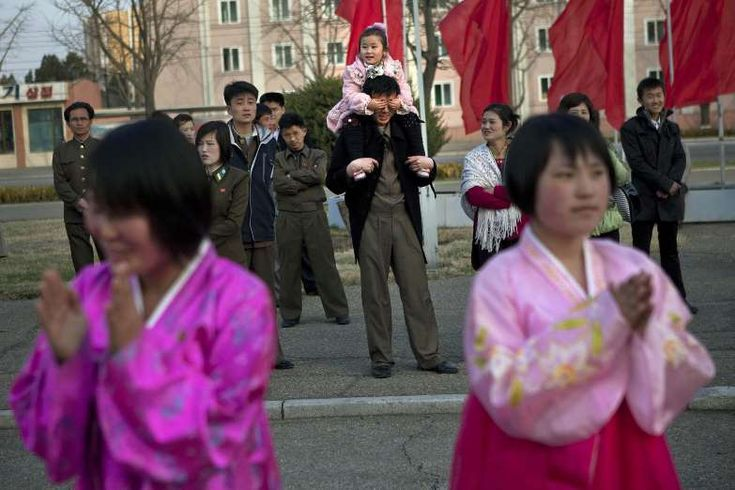 A North Korean child covers the eyes of her father as she sits on his shoulders watching mass folk dancing in front of Pyongyang Indoor Stadium in Pyongyang, North Korea. Oblivious to international tensions over a possible North Korean missile launch, Pyongyang residents spilled into the streets Monday to celebrate a major national holiday, the birthday of their first leader, Kim Il Sung.