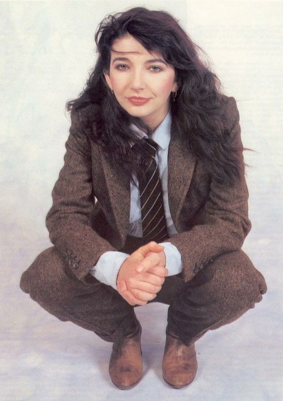 Kate Bush (known for her 1978 album The Kick Inside)  This is a strange portrait because she is squatting and wearing men's clothes.  I like the unusual nature of this photo and her simple grin and pose.