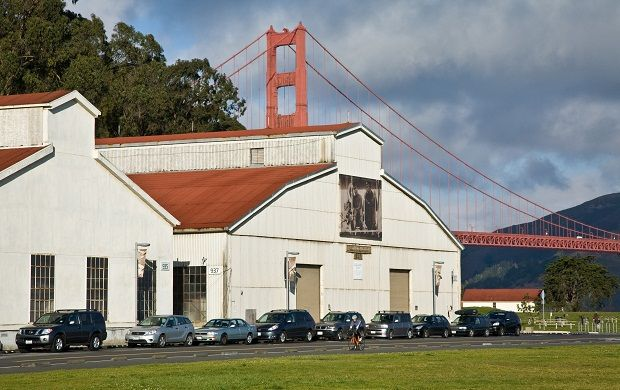 Two hangars on Crissy Field, large white buildings with two tiered slanted roofs, large windows, and garage size entrances.