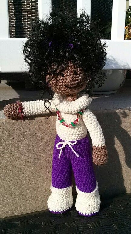Shay is posing for the camera outside on a beautifully mild and sunny day with her casual turtle neck sweater, purple pants and high curly ponytail.