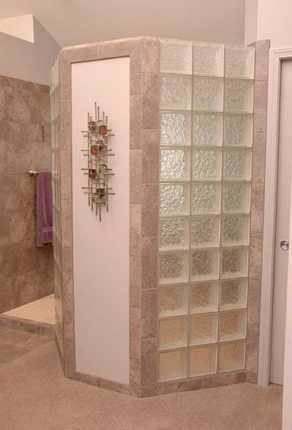 This doorless walk in shower design has a glass block privacy wall.