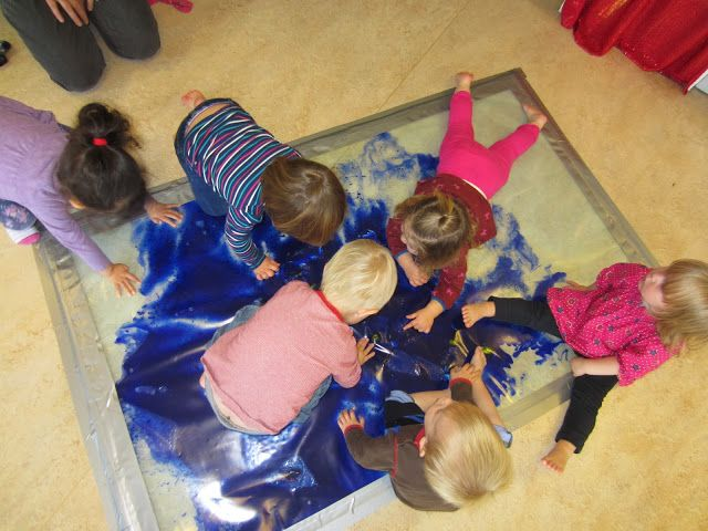 Fold a tarp in half. Full with paint, glitter, etc. duct tape. Allow children to explore this GIANT sensory bag!