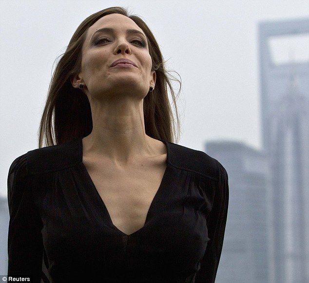 Smile for the cameras! Angelina Jolie strikes a pose as she speaks with press...