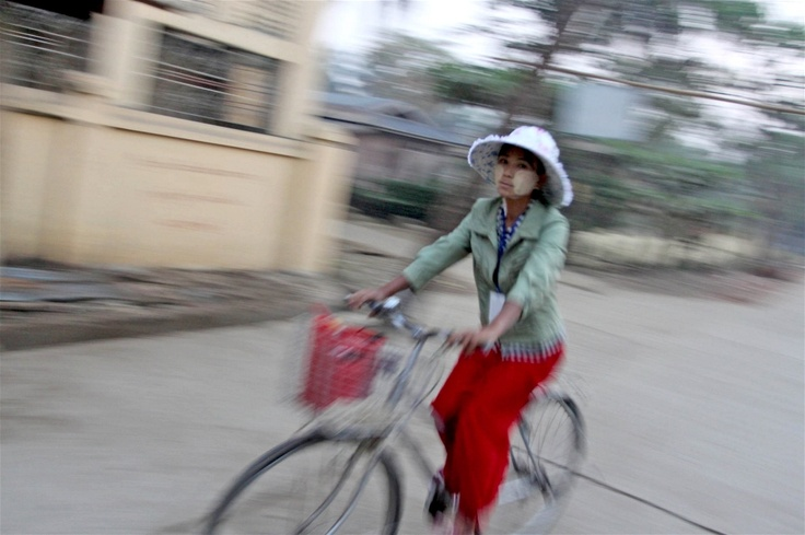 A woman wearing a traditional wood-based cream to protect her face rides a bicycle to work in Yangon (March 2012)