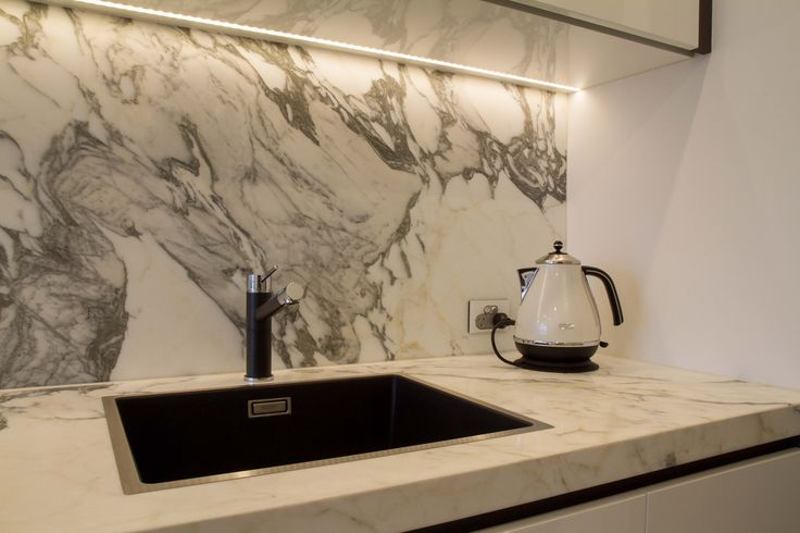 A modern, sophisticated, handle-less kitchen with marble benchtop and splashback. www.thekitchendesigncentre.com.au @thekitchen_designcentre