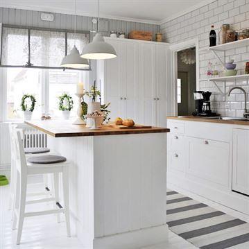 Mysigt lantkök med en vit helkaklad vägg och en vägg i gråmålad träspont. Barstolar från Ikea. Matta från Hornbach. Hissgardiner och lampor från Ellos.