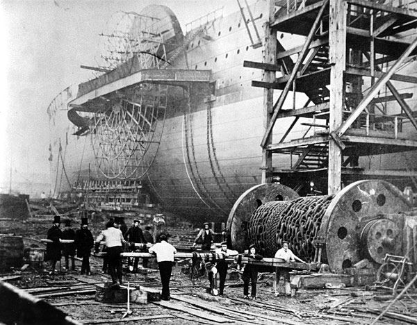 SS Great Eastern in 1858, Isle of Dogs, London, England, before its first launch on January 31, 1858. The Great Eastern, designed in part by Isambard Kingdom Brunel, was the largest iron sailing steamship at the time. Note the large paddle visible on the side of the ship. The Great Eastern was the first ship to be equipped with a steering engine. Apart from being memorable for its size and design, the Great Eastern is also notable for laying the first lasting transatlantic telegraph cable…