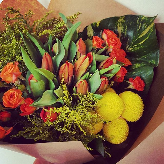 A modern style bouquet with clusters of orange and yellow - orange spray roses, orange parrot tulip, yellow solid, yellow pompms and tropical leaf.