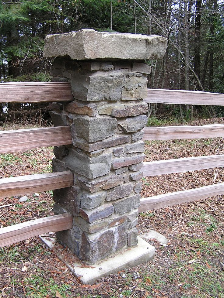 this stone column is part of a split rail fence that travels along the ...