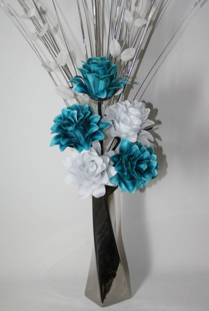 STUNNING ARTIFICIAL TEAL WHITE FLOWER ARRANGEMENT IN VASE. This contemporary artificial flower arrangement comprises of two white and three teal dragon flower heads. The arrangement comes complete with white leaf stem, silver spray grass teamed with a modern 25cm silver twist ceramic vase.   eBay!