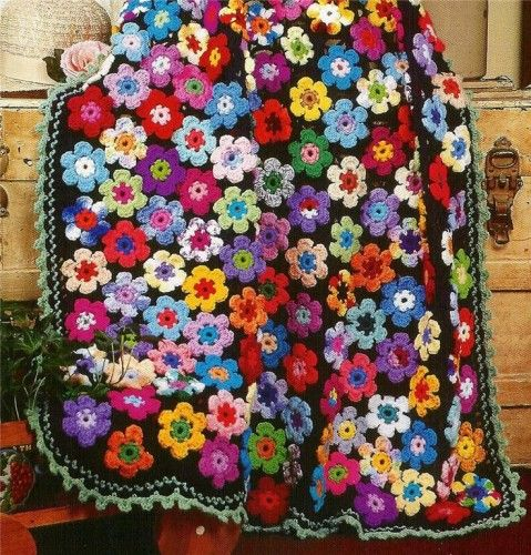 I love to make flowers but don't know what to do with them. I bet I could sew them onto a dark fleece blanket and add a pretty border. Looks like this background it crocheted.