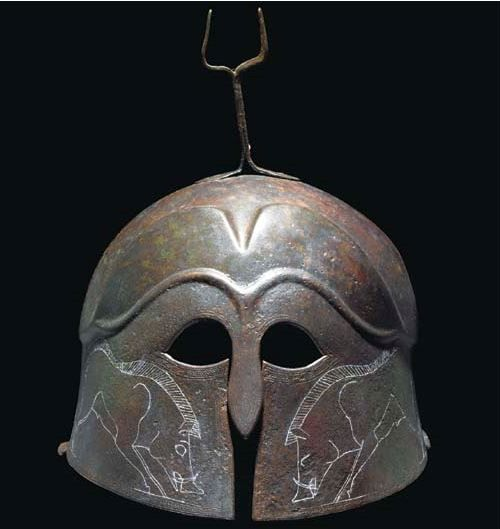 Pseudo Corinthian helmet, Magna Graecia, classical period, 5th cent. B.C. With everted rear flange, the moulded eyebrows extending into carinated crown perimeter, with false eye-holes and short nose-guard, the cheekpieces incised with confronting boars and vegetal motifs, a band of chevron around the perimeter, tall plume holder riveted to the crown, slight restoration and incised detail highlighted later in white, 24 cm high. Private collection, from Christie's auction