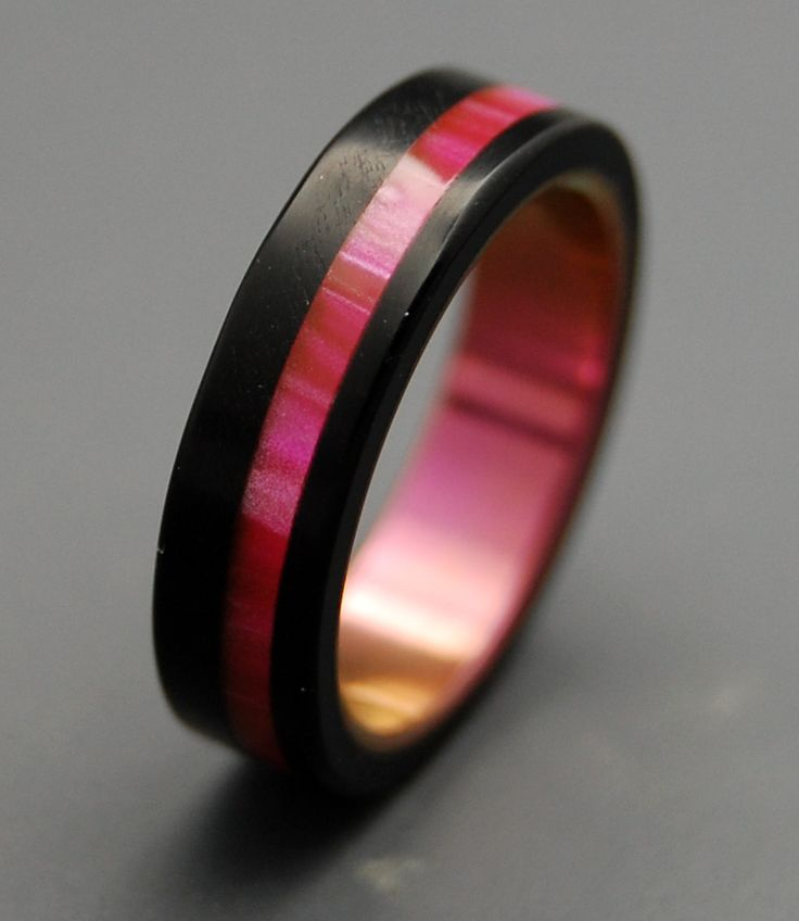 Melt for modern style. This gorgeous band is made from pure titanium overlayed with two types of resin. Solid black-sheen resin is offset by a shining Pink Opalescent overlay. A matching anodized inte
