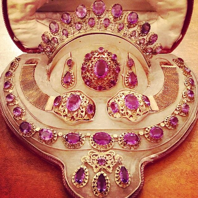 FRANCE_A 1820s three colour gold and amethyst grand parure comprising a tiara a pair of earrings a brooch, two bracelets and a necklace with girandole pendant. French.