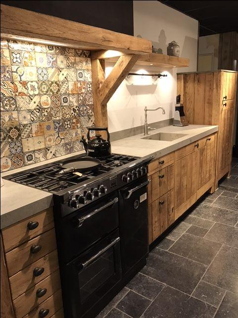 Landelijk robuust houten keuken met zwart stoves fornuis en keramiek blad