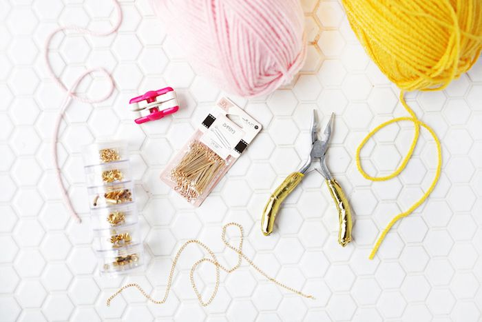 pastel pink and yellow, knitting woolen thread, gift ideas for mom, making a bracelet, near pair of pliers, jewelry making pins, lobster clasps and a thin gold chain