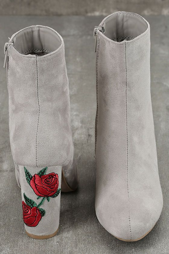 """Let your inner gypsy shine in the Gitana Light Grey Suede Embroidered Mid-Calf Boots! These trendy vegan suede booties have an almond toe upper, 7"""" zipper at the instep, and red floral embroidery at the heel."""
