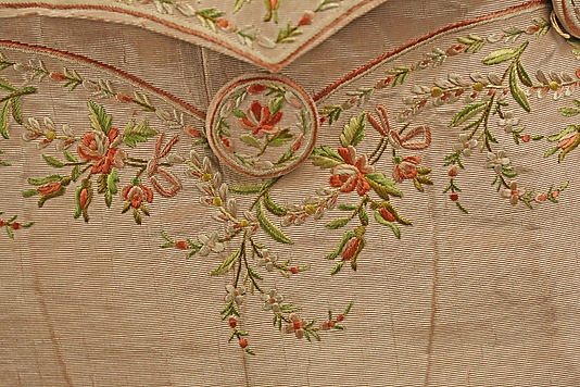 Detail of pocket flap embroidery & covered button. Suit, British, c 1780, silk. Metropolitan Museum of Art.