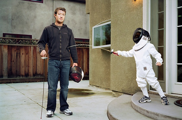 Mark Zuckerberg, holding a mask and a foil as a child in dry fencing gear stabs him from the side.
