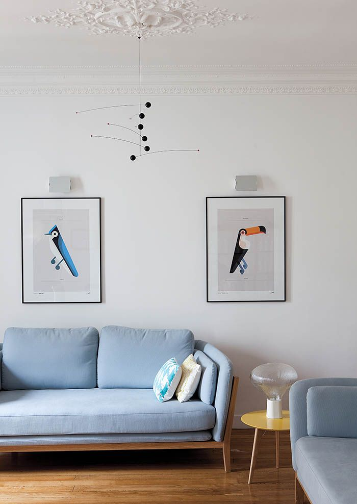 White living room with powder blue couch and mobile.