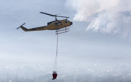 Two Working on Fire choppers assisted firefighters by water-bombing the flames on the mountain above Hout Bay on Tuesday 3 March 2015. Picture: Aletta Gardner/EWN.