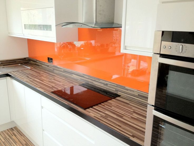 Orange coloured painted glass splashback livening up this kitchen.