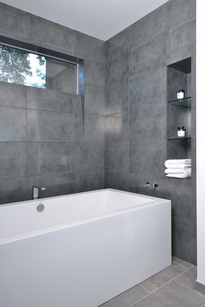 Keep it clean and simple with large-format gray tiles and a gorgeous big white bathtub. This cool and contemporary bathroom has a minimalist spa vibe that I find appealing and tranquil. If your budget doesn't allow for tile-clad walls, paint your walls a fetching shade of gray in an eggshell or semigloss finish instead