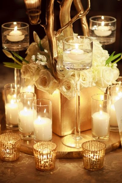 Remarkable table-scape, all white gilded in gold: square floral arrangement, candles of all sizes, mercury glass, and gold spray-painted curly willow branches.