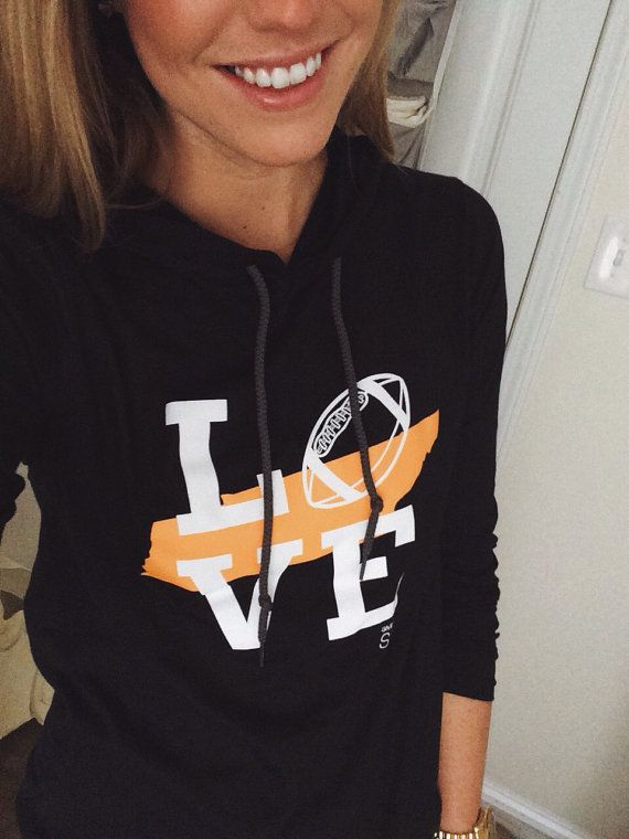 Love Tennessee Football Hoodie Perfect for every season - this lightweight long sleeve t-shirt has it all! You know you love the University of Tennessee Vols, so wear this black hoodie loud and proud to every football game. This womens hoodie is a classic piece, you will wear for years to come.