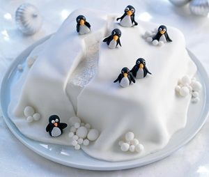 Iced cake with iceberg detailing and black and white penguins sitting on top