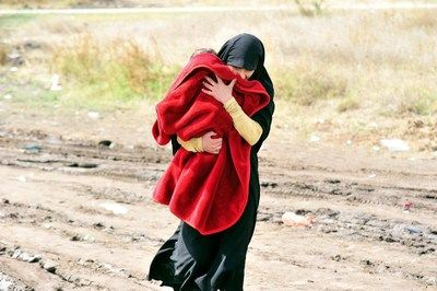 Une femme portant un enfant marche sur un chemin boueux de la ville m&