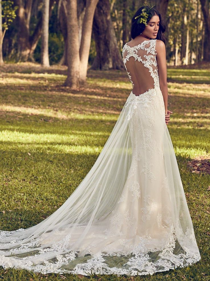 Maggie Sottero - BERNADINE, Beaded lace motifs dance over tulle in this sheath wedding dress, accenting the illusion plunging V-neckline, illusion straps, and illusion back with keyhole. Finished with covered buttons over zipper closure. Detachable tulle train accented in lace motifs sold separately.