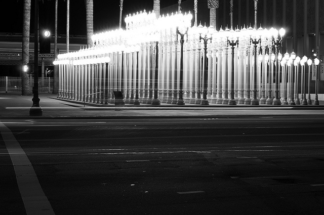 """Urban Light"", LACMA Museum.  202 restored cast iron antique street lamps, viewed at the LACMA museum in L.A.  ""This forest of city street lights, called ""Urban Light"" was created by artist Chris Burden. Despite initial appearances, the arrangement is not a perfect grid. Depending on where the viewer stands, the lamps arrange themselves in different angles and arrays."