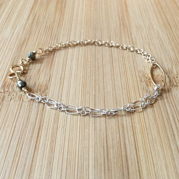 A double strand of sterling silver Figaro chain and 14K gold-filled cable chain meet at a central gold-filled, large marquise link. This is an elegant bracelet that works well on its own or stacked with others. The bracelet is 6.75 long and fastens with a gold-filled clasp. The clasp is marked with two faceted pyrite stones, introducing another subtle metallic hue to the piece. The mix of silver and gold makes for a versatile and visually textured bracelet. Check out more WildGingerJewelry…