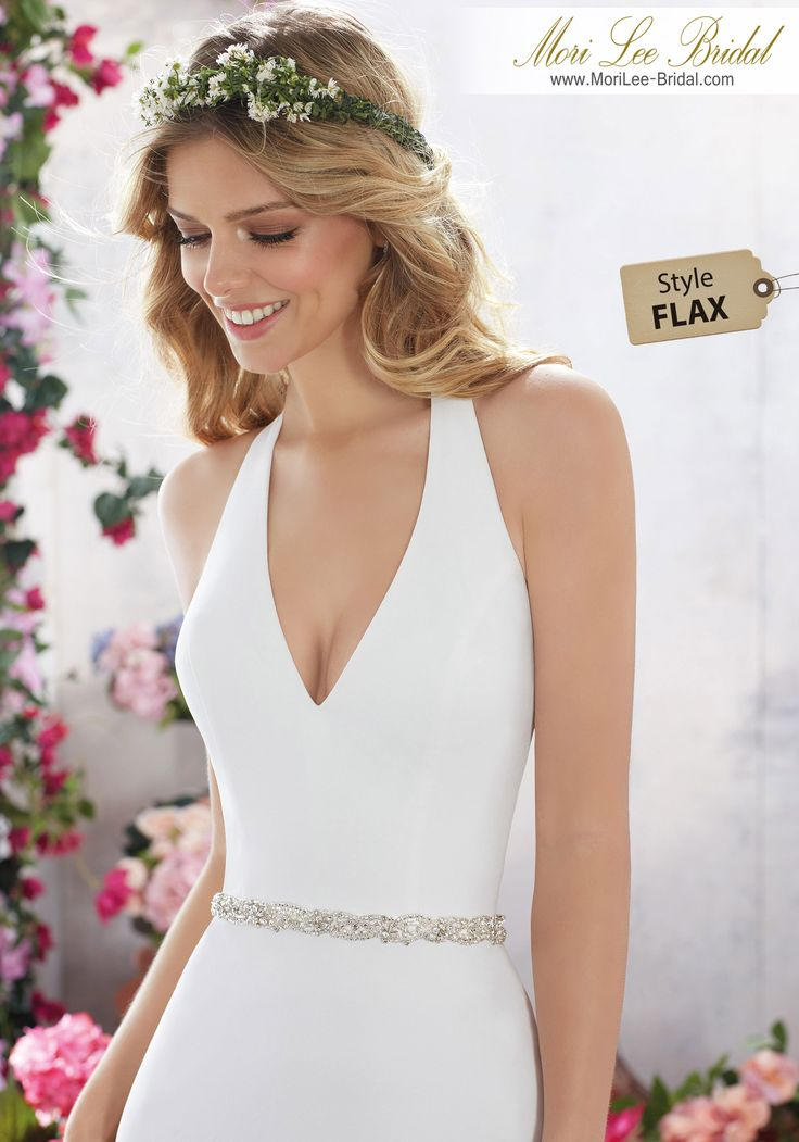 Style FLAX Melanie Wedding Dress  Simple and Understated, This Stunning Crepe Sheath Features a Flattering Halter Neckline and Jewel Beaded Belt for an Added Touch of Sparkle. Open Back Accented with Beaded Criss-Cross Strap Detail. Removable Beaded Crepe Belt Included. Colors Available: White/Silver, Ivory/Silver. Shown in Ivory/Silver.