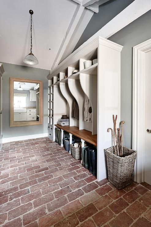 Long rustic mudroom features a vaulted ceiling over white mudroom lockers, one for each family member, next to a tall shoe cubbies atop a brick paver floor.