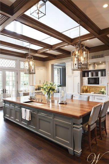 Neo-classical kitchen with wood island and white cabinetry. Architecture by New Canaan architecture firm Wadia Associates and interior designer Cindy Rinfret.