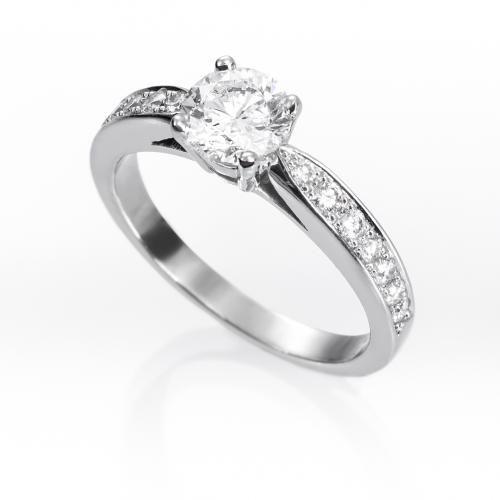 Anillo solitario de diamantes ROYAL Sortija de oro blanco 18 kts. estilo solitario montada con diamante central talla brillante engastado en garras, acompañado por diamantes talla brillante en los laterales.