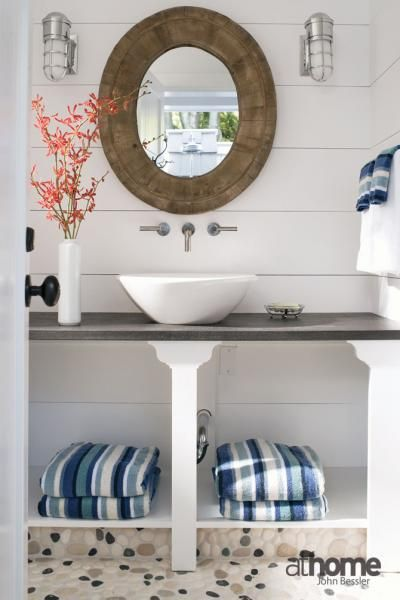 Beachy outdoor bathroom with white wood paneled walls and mosaic pebble floor.