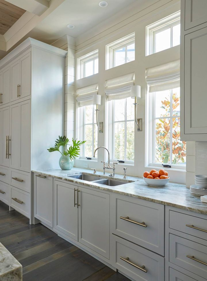 over the sink lighting. the light gray kitchen cabinets are adorned with extra long satin nickel pulls a stainless steel dual sink stands under row of windows dressed in over lighting