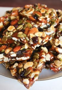 Autumn Brittle   1 Cup Almonds1 Cup Cashews3/4 Cup Pumpkin Seeds2/3 Cup Dried Cranberries2 and 1/2 Cups Palm Sugar1/2 Cup Honey1 Cup Water1/2 Teaspoon Salt1 Tablespoon Butter or Ghee