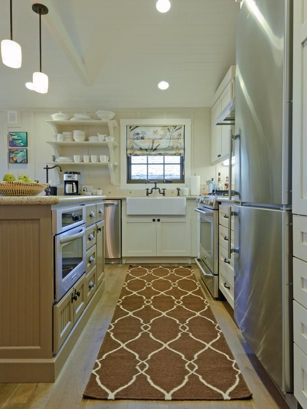 A modern farmhouse sink, mixed with contemporary furnishings, brings a lighthearted touch to this small kitchen designed by Regan Baker.