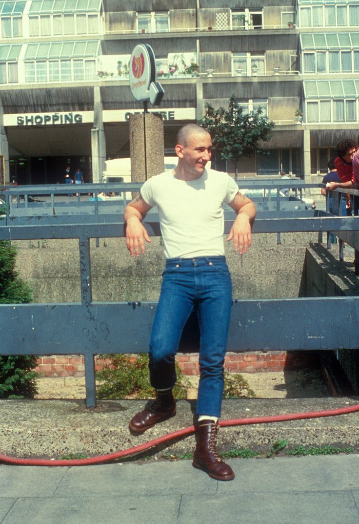 A teenage skinhead boy, wearing Doc Marten boots, Standing in the street, UK 1980's. ©Gavin Watson/PYMCA