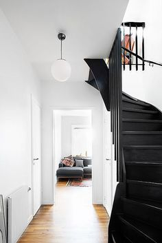 black staircase and white walls with globe pendant…