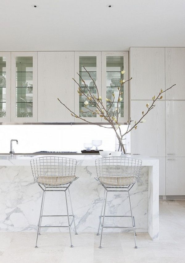 12 Kitchen Counters: There's nothing more classic for a kitchen. The white cabinetry with glass shelves, solid Carrara marble island, and Bertoia stools are fresh and timeless.