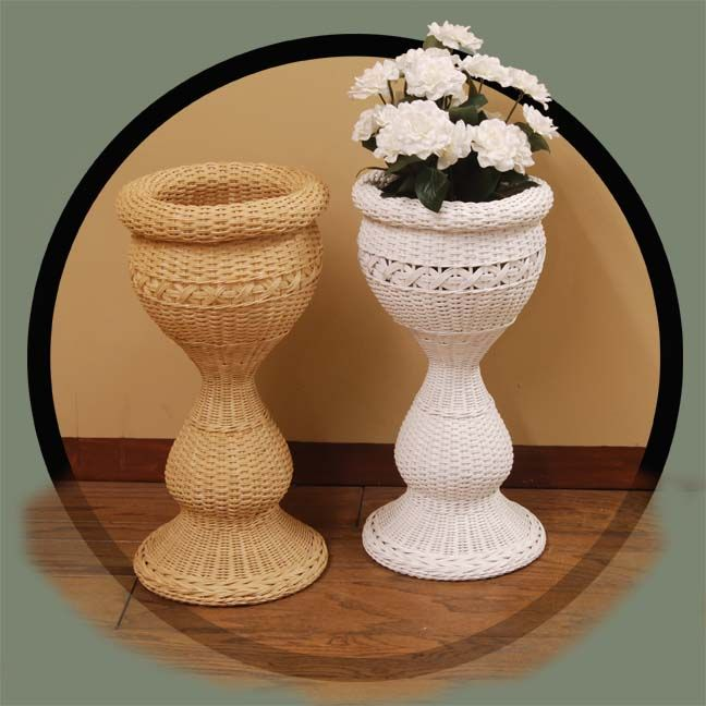 Round Wicker Pedestal Planter Lean close and smell the blooms that will certainly thrive in this beautiful pedestal planter. A flared circular base fans outward to support the exquisite shaping that rises to a large bowl container with broad rolled edging. Crafted in rattan wicker, it takes on heirloom properties with traditional weaving complemented by matchstick accents and rope-style braiding. Indoors, it brightens with colorful flowers of the season or with trailing vines all year long.